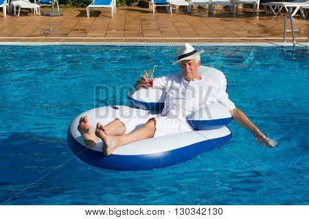 wealthy man relaxing in own swimming pool