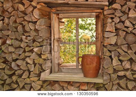 stacked firewood around a wooden window - closeup