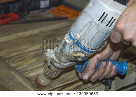Electric drill in man's hands. The process of drill working. Hands hold electric drill.