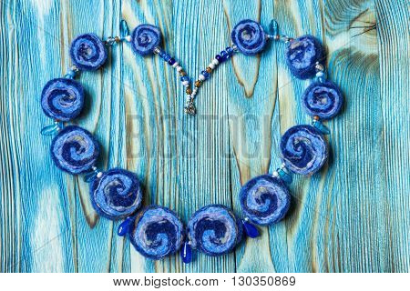 Handmade necklace of colorful beads of wool, colorful felt dried balls. Colored felt handmade beads on beautiful wooden background