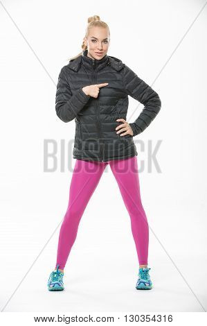 Attractive blonde in the sportswear stands on the white background in the studio. She wears cyan-yellow sneakers, pink pants and black jacket. She holds left hand on her waist, her right finger specifies on her chest. She looks into the camera. Vertical.