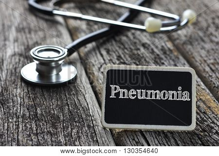Medical Concept-Pneumonia word written on blackboard with Stethoscope on wood background