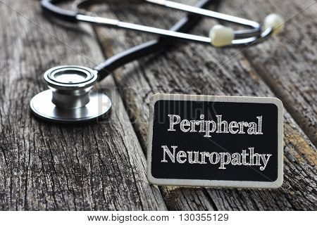 Medical Concept- Peripheral Neuropathy word written on blackboard with Stethoscope on wood background