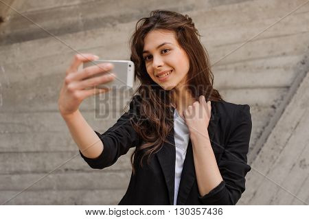 Selfie time. Young smiling  lady doing selfie on phone