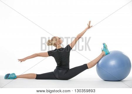 Attractive blonde girl in the sportswear with a blue fitball on the white background in the studio. She wears cyan-yellow sneakers, black pants and black t-shirt. She makes the splits: right leg is on the fitball and left leg is on the floor, arms stretch