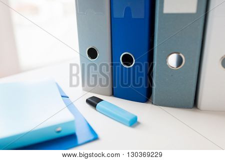 business, document, paperwork, office supply and education concept - close up of ring binders and files with highlighter pen or marker on table