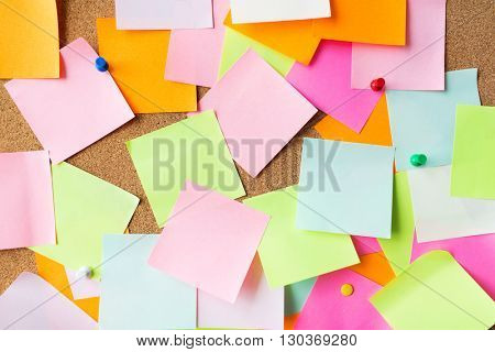 business, information, memo, management and education concept - close up of blank paper stickers on cork board