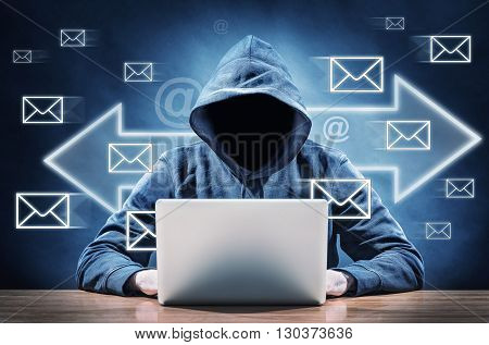 picture of a faceless person on a computer sending spam mails