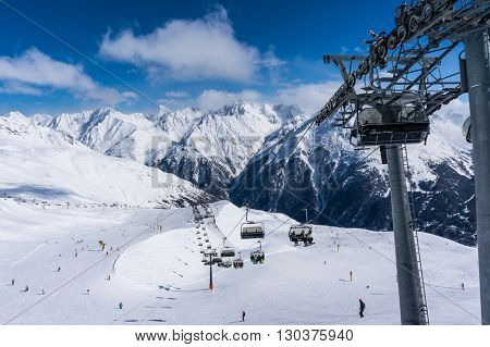 SOLDEN, AUSTRIA - 9 MARCH 2016: Skiers and double chairlift in Alpine ski resort in Solden
