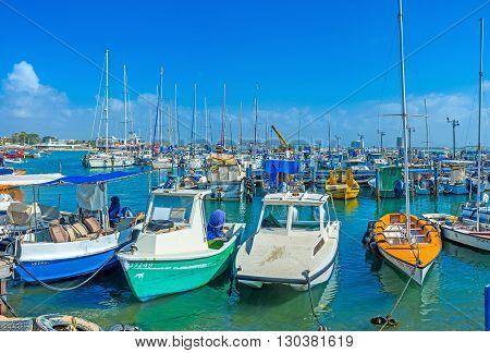ACRE ISRAEL - FEBRUARY 20 2016: The colorful fishing boats rocking on the waves in marina of Akko on February 20 in Acre.
