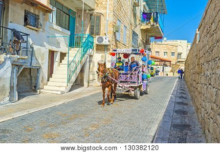 ACRE ISRAEL - FEBRUARY 20 2016: The tourist carriages with horses are very popular attraction in old Akko to discover the narrow streets fortress walls and medieval landmarks on February 20 in Acre.