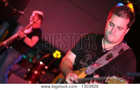 Selective Focus On Guitar Player With Bass Player In Background Playing A Rock Show