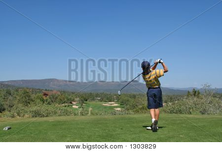 Young Golfer Hitting A Golf Ball Tee Shot In The Mountains