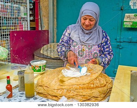 ACRE ISRAEL - FEBRUARY 20 2016: The elderly muslim arabic woman cooks the traditional flatbread in the Turkish Bazaar on February 20 in Acre.