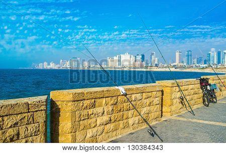 The fishing rods on the city promenade with the view on city of Tel Aviv on background Israel.