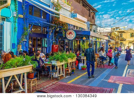 TEL AVIV ISRAEL - FEBRUARY 25 2016: The flea market neighborhood of old Jaffa is full of the cozy cafes decorated with plants in pots colorful rugs and wooden details on February 25 in Tel Aviv.