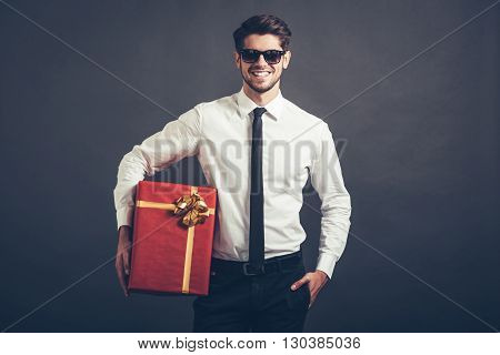 My congratulations! Cheerful handsome well-dressed young man holding gift box and looking at camera with smile while standing against grey background