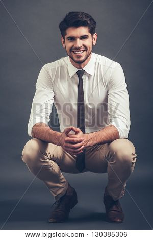 Elegant and cheerful. Full length of confident young handsome man looking at camera with smile while sitting crouched against grey background