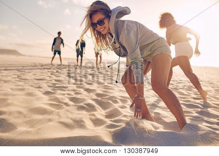 Young Woman Running Race With Friends At The Beach