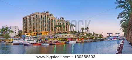 EILAT ISRAEL - FEBRUARY 23 2016: The view of marina entrance with the drawbridge and the huge hotel complex in the evening lights on February 23 in Eilat.