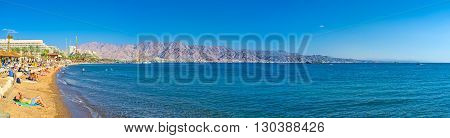 EILAT ISRAEL - FEBRUARY 23 2016: The scenic coastline with the comfortable sand beach and picturesque rocky mountains of Aqaba on the background on February 23 in Eilat.