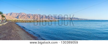 Panorama of the coastline of Eilat with the clear water surface and mountains of Aqaba on background Israel.
