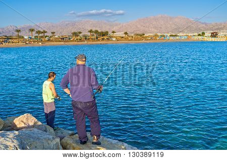 EILAT ISRAEL - FEBRUARY 24 2016: The men go fishing from the pier with the mountain landscape of Aqaba on the background on February 24 in Eilat.