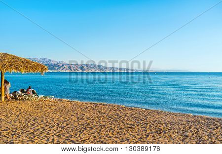 The sand beach in Eilat with the scenic Aqaba mountains on the background Eilat Israel.