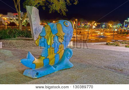 EILAT ISRAEL - FEBRUARY 23 2016: The golden symbols of luck are painted on the sculpture of the fish in front of Eilat Museum on February 23 in Eilat.