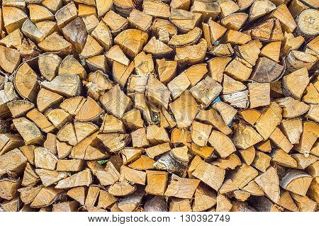 Firewood texture background. Chopped firewood birch poplar and larch stacked in woodshed and snowbound