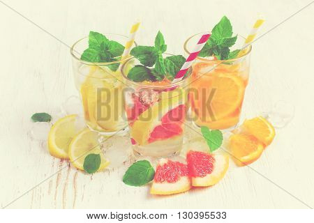 Refreshing summer drinks water with ice and lemon orange and grapefruit tinted
