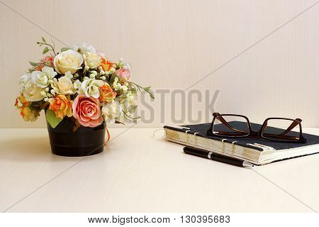 Artificial flowers and set of a black notebookglasses pen on wood table blackground.