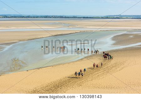 FRANCE MONT SAINT MICHEL - SEPTEMBER 26: View from walls of Mont Saint Michel on the bay during the low tide with groups of tourists walking. France on September 26 2015