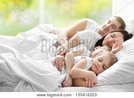 Family sleeping in bed on abstract nature background