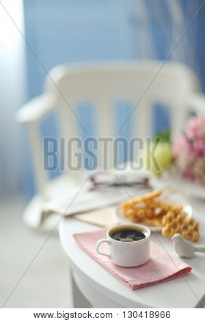 Cup of coffee with wafers on white table in light interior