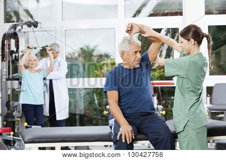 Nurse Assisting Senior Woman In Arm Exercise In Rehab Center