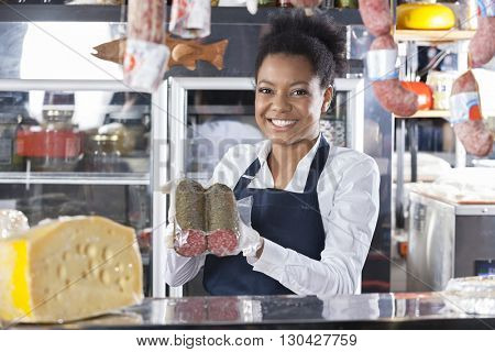 Happy Young Saleswoman Showing Cheese At Counter