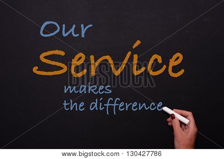 woman writes on blackboard our service makes the difference