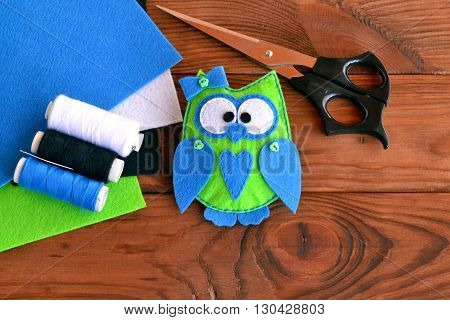 Felt owl pattern, bird toy play, owl ornaments, sewing plush toy. Hand fabric diy. Felt animal gift. Scissors, thread, needle, colorful sheets of felt on a wooden table