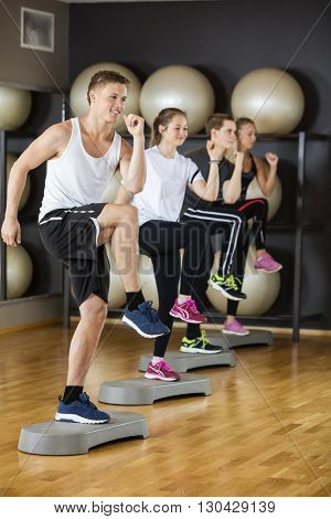 Friends Performing Step Exercise In Gymnasium