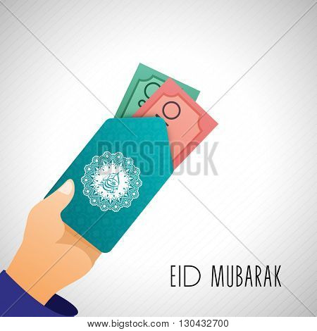 Human hand holding money envelope on shiny grey background, Concept for Muslim Community Festival, Eid Mubarak celebration.