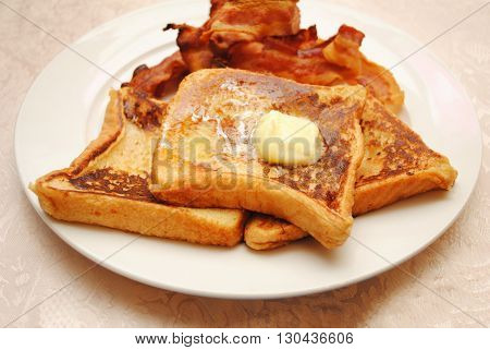 French Toast with Butter Served with a Side of Crispy Bacon