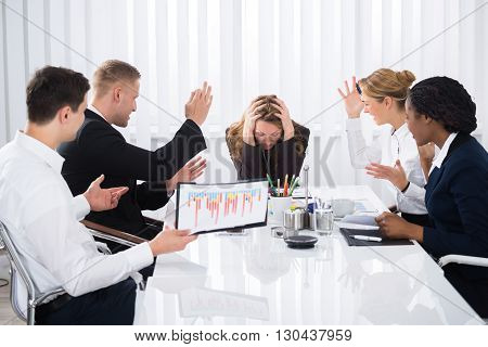Upset Businesswoman Sitting With Aggressive Colleague In Meeting