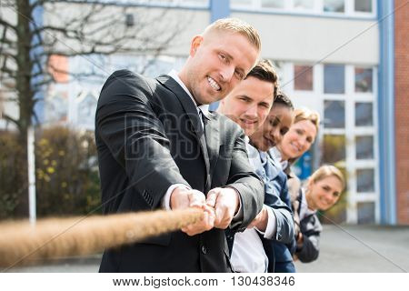 Group Of Multiethnic Businesspeople Pulling Rope Playing Tug Of War poster