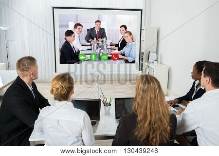 Group Of Businesspeople Together Videoconferencing At Workplace