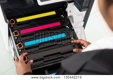 Young African Businesswoman Fixing Cartridge Near Photocopy Machine In Office