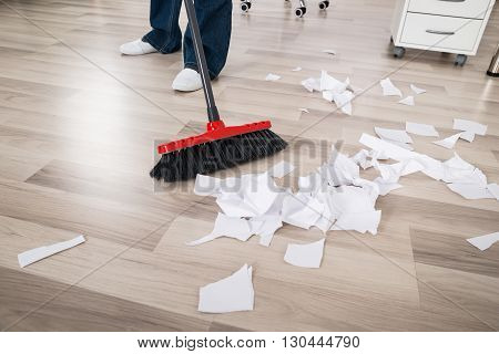 Close-up Of A Janitor Sweeping Torn Paper Pieces On Hardwood Floor