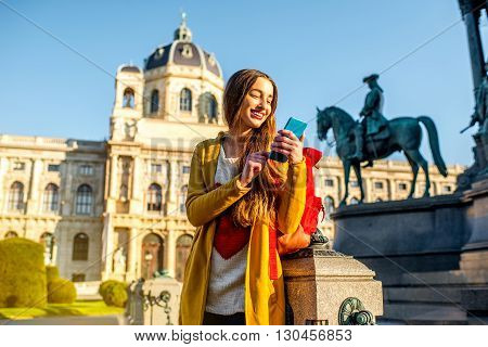 Young female tourist with smart phone on Maria Theresa square near museum of Natural history in Vienna. poster