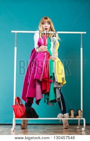 Amazed shocked woman girl taking grabbing all clothes coats and shirts in wardrobe. Surprised young girl shopping in mall. Fashion clothing sale concept.