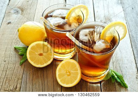 Two Glasses Of Cold Iced Tea With Lemon Slices On A Rustic Wood Background